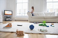 Girl 5-6 watching television toys on floor in foreground (thumbnail)