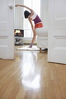 Woman exercising and watching television in living room back view