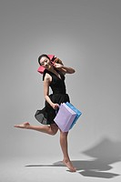 young woman holding shopping bag and doing ballet, studio