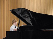 Pre teen boy playing piano in music class (thumbnail)