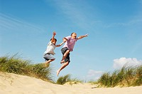 Father and Son holding hands jumping of sand dune at beach low angle view