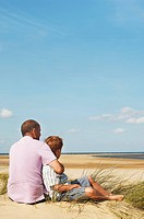 Father and Son sitting on sand dune looking out on Beach back view (thumbnail)