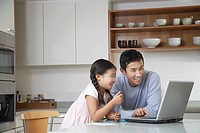 Father and daughter playing with laptop on kitchen counter