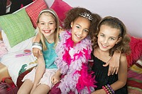 Girls sitting arms around one another on trendy sofa at a Slumber Party high angle view