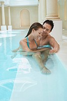Young couple talking at edge of swimming pool (thumbnail)