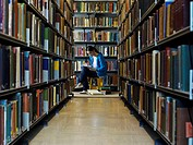 Young woman reading by bookshelf in library (thumbnail)