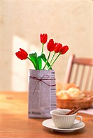 Red tulips wrapped in newspaper on a breakfast table
