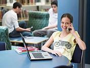 Teenage using mobile phone sitting in library (thumbnail)