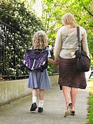 Elementary schoolgirl walking with mother on pavement back view