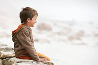 Boy 5_6 sitting on wall on beach