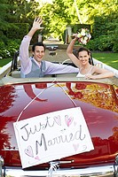 Mid adult bride and groom in retro car waving hands (thumbnail)