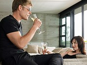 Young man and woman drinking champagne in living room