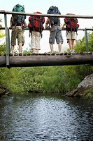 Four teenagers 16_17 years standing on bridge carrying backpacks looking down back view