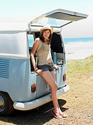 Young woman leaning on open tailgate of van