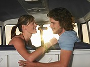 Young couple face to face in front seat of van