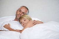 Couple hugging lying in bed