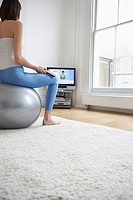 Woman sitting on fitness ball watching television back view