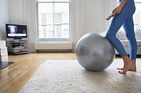 Woman standing at fitness ball watching television low section