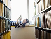 Student lying down on windowsill in library reading (thumbnail)