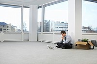 Office worker contemplating phone sitting on floor of empty office space side view