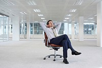 Office worker sitting in swivel chair hands behind head in empty office space