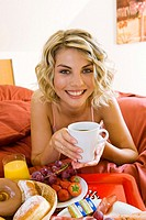 Young woman has breakfast in bed
