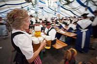 Senior waitress with beer steins during Oktoberfest, Munich, Bavaria, Germany