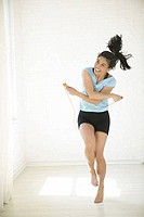 Young woman jumping with rope