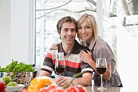 Couple in kitchen drinking wine