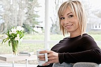 Woman holding coffee mug in living room