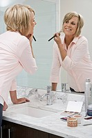 Middle_aged woman putting on makeup