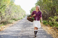 Woman walking with a basket of fresh produce on a country lane