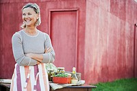 Middle aged woman ready for an outdoor meal beside a barn