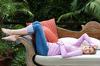 Young woman relaxing on outdoor sofa