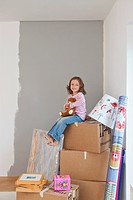 Little girl sitting on boxes in partially painted room