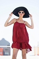 Fashion model standing and holding a sun hat