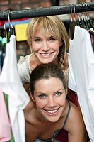 Two women hiding behind a clothes rack in a boutique