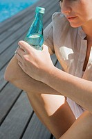 Woman sitting on a boardwalk and holding a water bottle