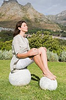 Woman meditating on round stones