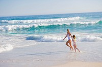 Woman running on the beach with her daughter (thumbnail)