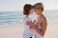 Woman with her daughter rubbing noses on the beach