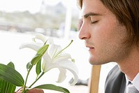 Close_up of a groom smelling a lily flower
