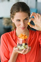 Close_up of a woman holding fruit salad