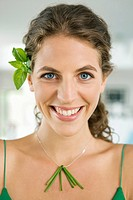 Woman smiling and wearing vegetable leaves in the kitchen