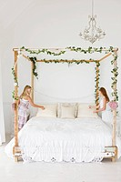 Two girls decorating a bed