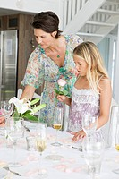 Woman arranging a table for a party with her daughter
