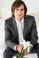 Groom sitting on the bed and holding a lily flower