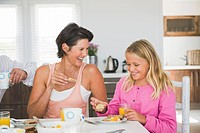 Woman having breakfast with her daughter at the dining table