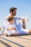 Man and his son drinking milk on the beach