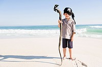 Boy in pirate costume standing on the beach